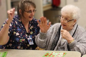Team member and resident playing bingo